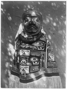 Woman Shaman wearing a fringed Chilkat blanket, a hamatsa neckring and mask representing deceased relative who
