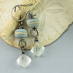 I love the organic beachy look of these earrings. Wire wrapped, carved rock crystals are suspended on artisan sterling silver connectors,