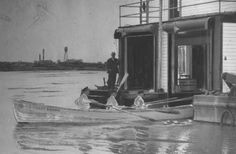 Man standing on life saving station on Ohio River. Three men are in the front and center in a U.S. Coast Guard row boat near Louisville. The first Louisville Lifeboat Station was a wooden houseboat built in 1881 and located at the Falls of the Ohio. It was replaced with a second wooden houseboat in 1902 and then with a steel-hulled houseboat in 1928. This was the only inland life-saving station in the United States and the only permanently located floating lifeboat station in the world.