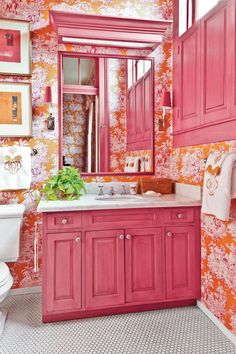 """Play with Pattern - 7 Small-Space Makeovers - Southernliving. Designer: Melissa Rufty    Size: 40 square feet  Before: A tired, all-white, utilitarian bath.  The Transformation: Magenta-and-orange toile wallpaper now envelops the room. """"We enlivened it by painting the cabinetry, trim, and shutters a pinkish red [Mardi Gras by Benjamin Moore],"""" says Melissa.  Small-Space Advice: """"Take the opportunity to splurge here; the quantity needed will be less."""""""