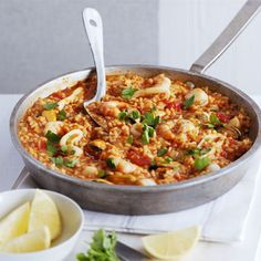 Easy Paella Recipe Main Course with olive oil, onions, hot smoked paprika, risotto rice, dry sherry, chopped tomatoes, chicken stock, frozen seafood, lemon, flat leaf parsley