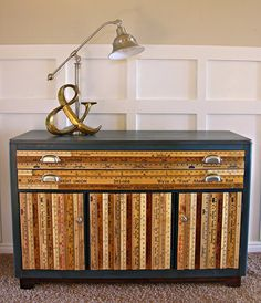 Use vintage yardsticks and rulers to cover (and spruce up) the front of an old piece of furniture. DIY project.