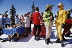 Snowmass Gathering. Slim Aarons. Two women, wearing brightly-coloured skiwear, stand in the foreground of a group of people attending a party in Snowmass Village, in Pitkin County, Colorado, in April 1968.
