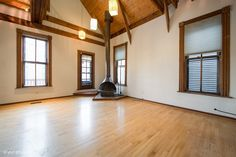 A wood-burning stove and vaulted ceiling with wooden rafters give this 3-bedroom duplex in Lakeview the charm of a cozy chalet. Enjoy an in-ground swimming pool and hot tub out back. #chalet #lakeview #chicago #apartments #stove #vintage