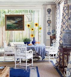 Boldly patterned curtains join painted bamboo chairs and a Maurice de Vlaminck seascape | archdigest.com