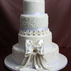 Keeping with Tradition 2082-Fondant frosting & decoration only.-Decoration: silk ribbon around each tier, alternating buttercream design, handmade pastillage roses & large pearlized fondant bow.