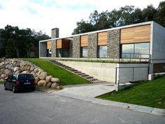 vivienda de volumen prismático, combinando el hormigón, la madera, el cristal y la piedra autóctona; configurada en dos plantas; sótano y baja.