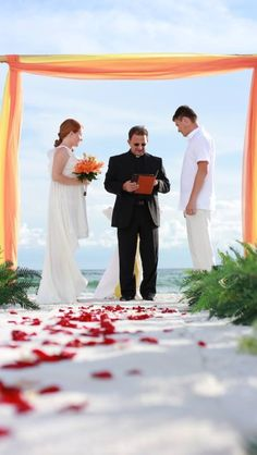 Orange bamboo beach wedding set with rosé petals. Fun Russian couple getting married.