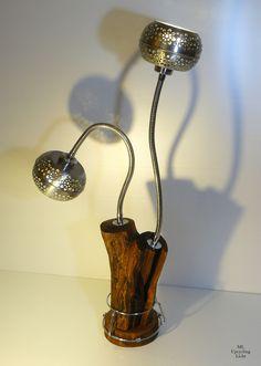 TWINLIGHT  Ein Obstbaumrest trägt die beiden zu Lampenschirmen umfunktionierten Windlichter. Mit den Schwanenhälsen lassen sie sich beliebig ausrichten. Ein ausrangiertes Edelstahlgestell umfasst den Sockel und passt sich dekorativ an.