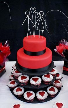 Two tier red wedding cake with two cupcake tiers and wired bride and groom toppers.JPG