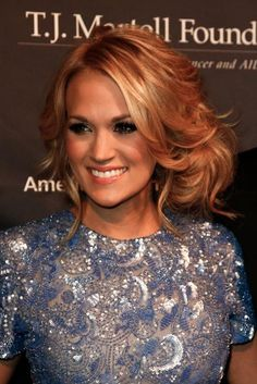 Gather waves into a loose, low bun at the nape of the neck, and gently pull shorter layers out of the bun to create a faux bob effect. #CarrieUnderwood #Hairstyles