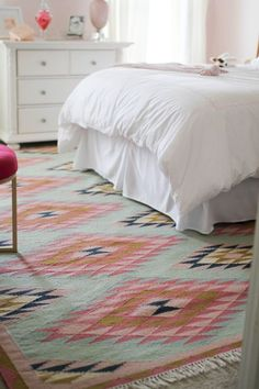 Take an all-white room up a notch (or two) with a patterned rug, like this one, that pairs mint with other cheery colors, including pink and gold.