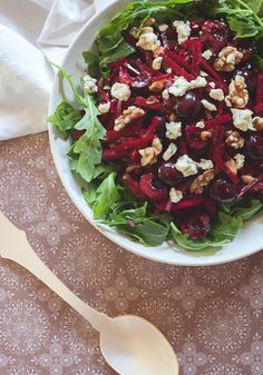 Potinara: SUMMER BEET AND SWEET CHERRY SALAD WITH TOASTED WALNUTS: Serves 6-8  1 cup cherries, halved and pitted 1 large shallot, minced juice of 1 lemon 4 medium beets, peeled 2 Tbsp. balsamic vinegar 2 tsp. maple syrup 4 Tbsp. extra virgin olive oil 1/4 cup walnut halves, toasted 1/3 cup blue cheese (French, Danish or Stilton) crumbled arugula sea salt and freshly cracked pepper to taste