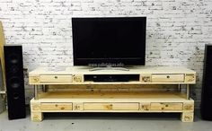 This one is an idea of creating a huge TV stand made up of wooden pallets; there are multiple drawers in it to store the items such as remote of the TV. There is just one hollow space for the DVD player and a person can add more hollow spaces if there are more products to place.