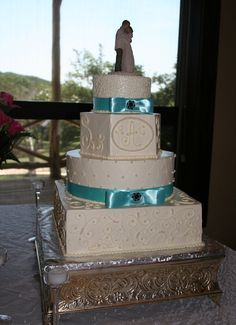 Different shaped tiers and piping design add interest to this unique wedding cake