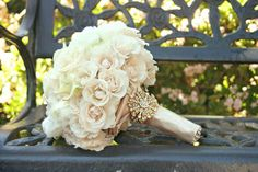 Vintage bouquet with soft colours like white, ivory, cream, and big blooms like hydrangeas, peonies, or roses. Pearls, lace, and a sparkly brooch on the stem complete the creation.