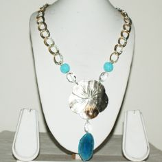 Decorative Real Shell Necklace with a Smart Blue Onyx Pendant Embellished with Textured Turquoise Balls and Crystal on a Double Metal Chain Finished in Silver and Gold.