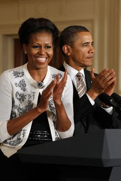 The First Lady plays up her lace floral patterned cardigan with a simple rose brooch.