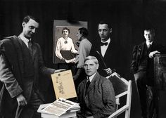 From left to right: Max Ernst holding a copy of Die Schammade, in the background Heinrich Hoerle paints a portrait of his wife Angelika (both editors of Der Ventilator on the table.) They left the Dada group and created the group Stupid). Sitting the painter Otto Freundlich. Standing and behind, Johannes Baargeld, and right to the bottom Hans Arp who came to Cologne in February 1920.