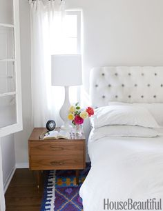 A vintage Lane nightstand on a Moroccan rug from Anthropologie flanks a Barrett-designed headboard in white denim.