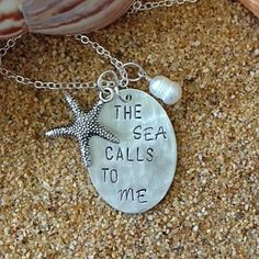 """I've hand stamped """"The Sea Calls To Me"""" on a 3/4 inch x 1 1/4 inch Sterling Silver disc and textured the piece with a hammer. A cream pearl is wire wrapped in Sterling Silver.Choose between a Tibetan Silver Starfish, Tibetan Silver Anchor, Bronze Anchor, Tibetan Silver Seahorse, Gold Starfish and Silver Sand Dollar.Please note, the picture above is a representation of the necklace you are purchasing. Each letter is personally hand ..."""