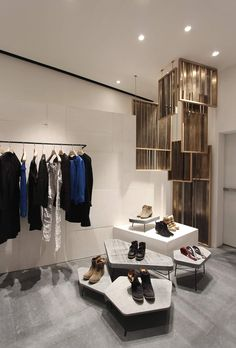 Store interior design for the fashion designer Isabel Marant. materials: floor: Hainaut blue stone walls: formwork cast plaster, mirror hanging racks: bent steel profiles with waxed finish fitting rooms: solid oak, brass cladding: solid oak wood structure and rotating brass louvers shoes and accessories display: drawn steel with waxed finish structure, high-pressure water waterjet cut …