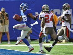 New York Giants WR Hakeem Nicks runs past Tampa Bay Buccaneers strong safety Mark Barron for a touchdown during the first half.