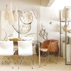 Dining room  The abstract artwork is the defining feature in this dining room. Natural materials match with the painting to produce an organic feel, while the metal and glass dining table and white dining chairs enhance the room's light, modern aspects.