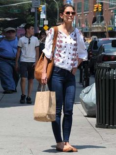 Katie Holmes out and about in Manhattan wearing blue jeans and a white, tribal-style blouse, June 2012.
