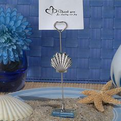 """A stylish way to greet and seat your guests at your beach themed event. Each place card holder has a silver seashell design charm accented with blue crystals and is attached to a metal stick holder seated on a crystal glass base. Available only from Cassiani collection, as your guests arrive to your special day they can be greeted and then seated by these unique place card holders that they can take home and use as stylish photo holders as well. Each place card holder measures 4.5"""" high."""