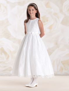 (7 Tea Length, White) A white First Communion gown is a symbol of the purity and beauty of your little girl's soul. This dress expresses those qualities and so much more! The sleeveless satin dress features a timeless and classic allover lace overlay. Adorned with a jewel neckline, wide satin waistband with side front bow and graceful box pleated dirndl skirt that is finished with a scalloped lace hem. This vinatage inspired lace and satin theme is simply breathtaking and a must have for…