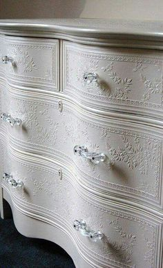 One of the best examples I've seen of a dresser (this one French Provincial) repurposed with embossed wallpaper and painted a pearlized white. Truly stunning!