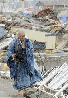 粉雪が舞う被災地を、祈りをささげながら歩く僧侶=4日午前、岩手県山田町