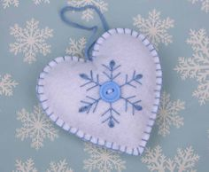Handmade felt heart Christmas ornament.  Blue and white scandinavian style Christmas heart decoration, Hand embroidered snowflake design with button detail, blanket-stitched edges and a loop for hanging.  9.5cm high.  White background with blue embroidery and button.  Please see separate listing for the blue heart here; https://www.etsy.com/listing/116049626/felt-christmas-ornament-scandinavian