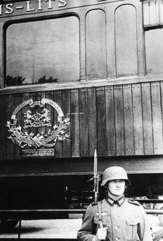 A German soldier in front of the railway wagon in which the armistice of 1918 was signed in the Forest of Compiegne. The wagon was brought back from his museum to the place where the 1918 armistice was signed, to end the fighting in the West. Signing of the armistice in Compiegne, 1940, World War II, Western Front, French campaign.