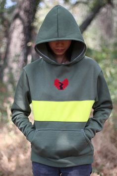 Fight or Mercy? What would you choose? This cosplay hoodie was inspired by Chara of the Undertale video game. It is a pullover style with long sleeves, a front pocket, and a hood. One iconic large str