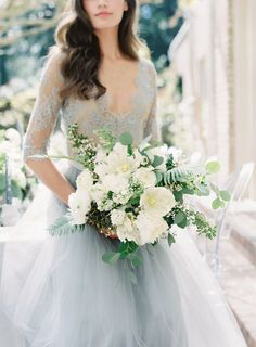 This verdant bouquet designed by Sinclair & Moore Events perfectly contrasted with the bride's regal ball gown. It features ferns, eucalyptus, viburnum, tulips, garden roses, spirea, and privet berry.