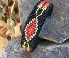 Twee veer Beaded Manchet armband ontwerpen in goud en tinten van rood op een zwarte achtergrond is handgemaakt door de kunstenaar met grote liefde en geduld. Het ontwerp is geïnspireerd door Native American kralen. Deze armband is mooi met elke outfit. De kralen techniek is loom