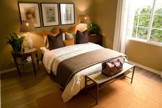 Cozy bedroom flush with warm tones of orange and brown, hardwood flooring, and bamboo style table at foot of bed.