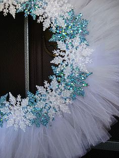 LOVE THIS!  A little inexpensive white tulle and some Dollar Tree glittery snowflakes and... Voila!  Winter wreath!