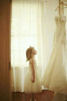 Picture of the Flower girl looking at the bride dress, this will be a great picture to give on her wedding day :)