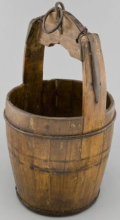 Antique Chinese wooden water bucket with iron ring at the top of bucket. Ring may have been used to lower bucket into and of out well or fas...
