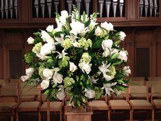 White altar arrangement. Roses, dendrobium orchids, hydrangea, lilies, white snapdragons.