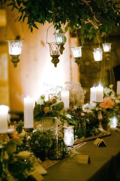 Green and white foliage teamed with gold linen and white candles setting off the inviting tablescape.
