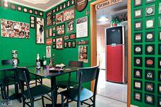 No lugar do sofá, duas mesinhas de madeira laqueadas, seis cadeiras na cor tabaco e duas banquetas altas (para o balcão) mobiliam o espaço com lugares para as visitas se acomodarem nesta sala de jantar que imita um pub irlandês e exibe porta-copos, rótulos emoldurados.
