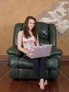 young female on couch using laptop. - Portrait of a happy young woman sitting on couch with laptop. Model: Brittany Beaudoin