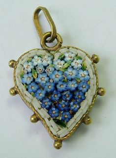A 1930s brass micro mosaic witches heart charm filled with tiny forget-me-not flowers.