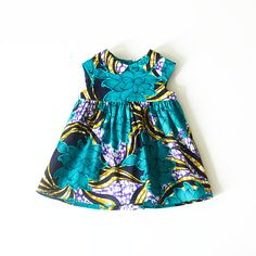 An adorable baby Ankara dress in a beautiful bright and bold turquoise flower African print fabric. It is a classical baby girls style with a gathered skirt, perfect for casual wear or that special occasion. Fully lined. Add a matching Bow Hair Clip at checkout for that extra special touch!