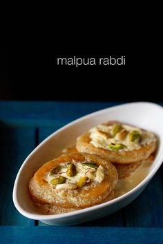 malpua rabdi - popular indian sweet of fried fluffy pancakes dipped in sugar syrup and served with rabdi or sweetened thickened milk.