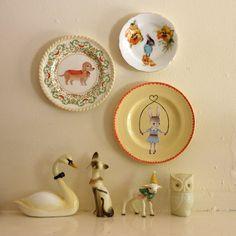 Vintage illustrated plates and porcelain figures.